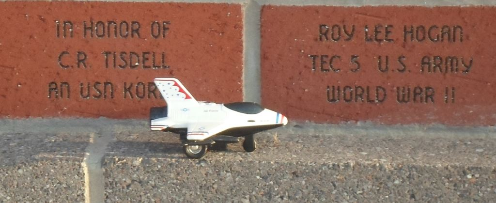 A small toy plane next to several memorial bricks