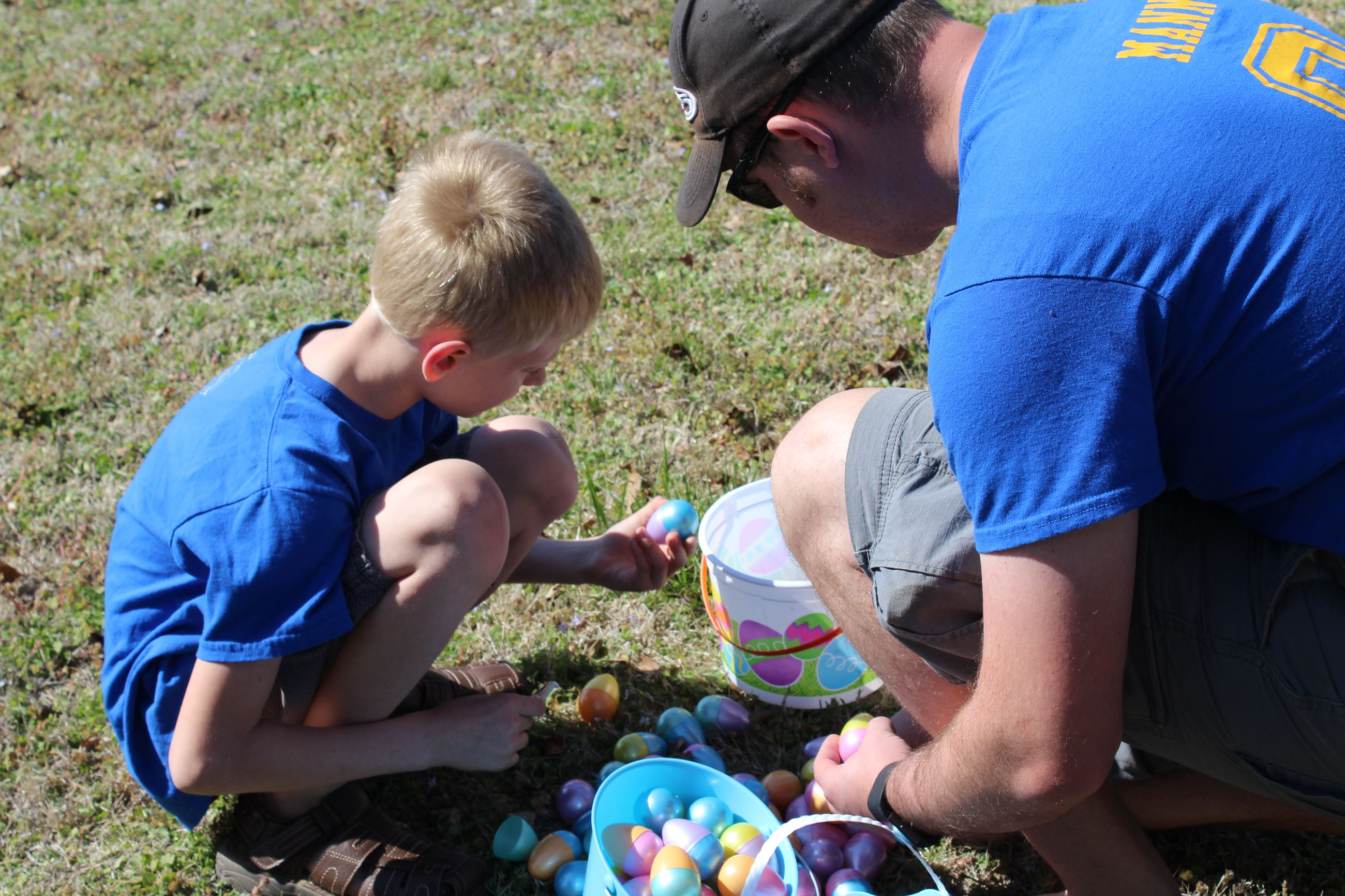 Easter Egg Hunt - A boy and father crouching and taking stock of easter eggs collected