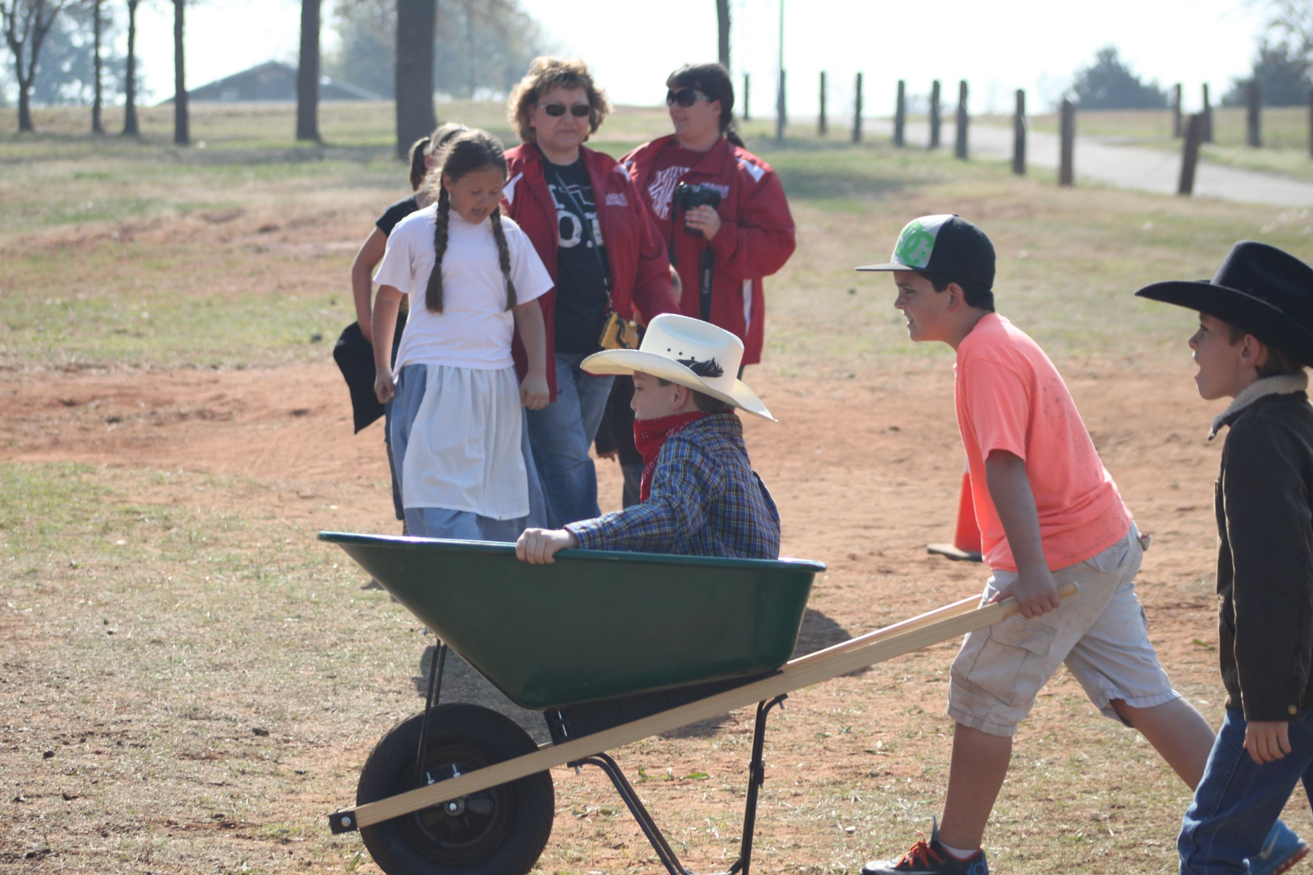 A boy pushes another boy in green wheelbarrow while others look on