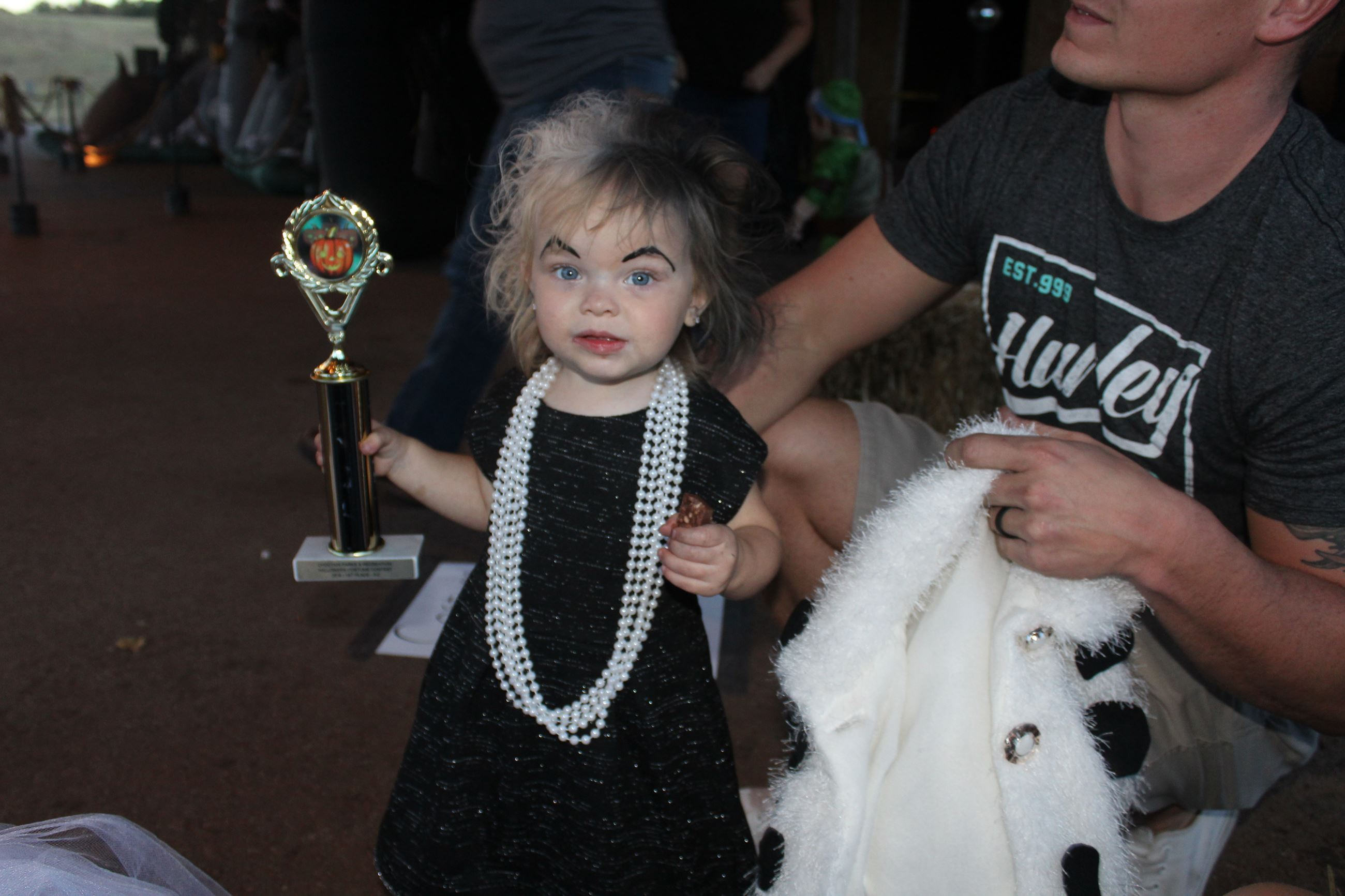 A young girl in costume holding trophy