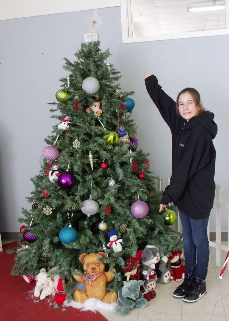 A girl showing off a Christmas tree