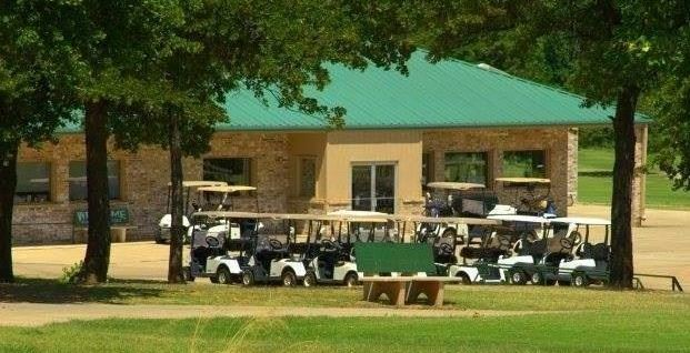 picture of the back of the golf course clubhouse with golf carts parked together